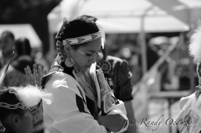This was taken at a pow wow in Grande Rond, OR.  As I was taking my camera out I looked up and saw this girl in the distance and thought it was the perfect picture.  I believe she was waiting for her turn to dance in some pow wow dance competition.