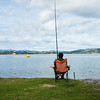Lady sitting in chair on edge of Ohiwa Harbour, fishing.