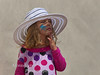 Little girl with painted face and big sun hat comtemplates the situation.