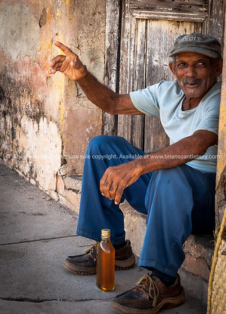 Sitting on doorstep, man waves from the door step of his home on side of street in Trinidad, Cuba. Model Release; No. Editorial or personal use only.