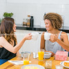 Breakfast time, at table two young women gift giving and happily laughing together.