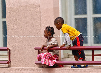 Kids playing on window ledge, watching more children on pavement, Paris. Model Release; No. Editorial or personal use only.