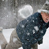 Middle aged man throwing a snowball at the photographer in a New England blizzard