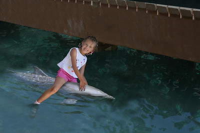 a young girl riding a dolphin in Mexico