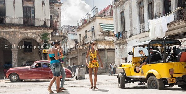 Havana, Cuban street scene with teenage girls crossing road. Model Release; No. Editorial or personal use only.
