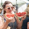 Woman at Saturday market holds watermelon