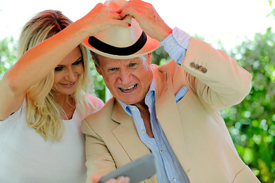 Older man taking a selfie with a younger woman for social media