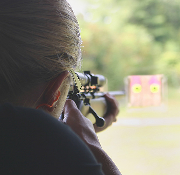 Woman shooting a rifle at a rifle range