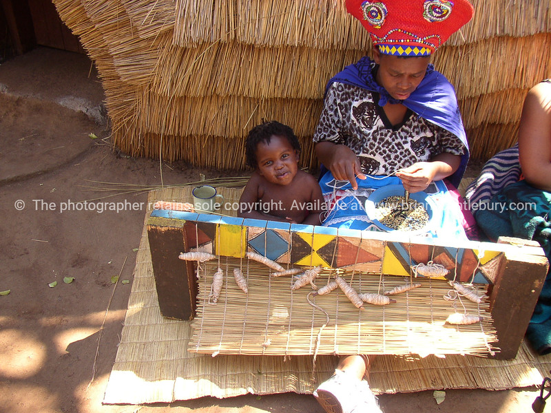 Craft being created. Child sits with mother while she creates another woven mat for the tourist trade. Model Release; No. Editorial or personal use only.