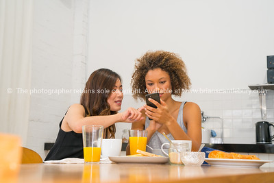 Breakfast time, at table two young women looking at mobile and taking selfie.