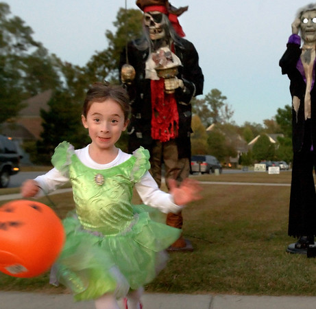 Gracie McDonald, 5, dressed as Tinkerbell, runs for her life as the ghouls behind her come to life at the Laughinghouse residence where Mrs. Laughinghouse sets out strobes on Halloween night.