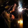 A tig welder concentrates on his work protecting his face from the bright arc light with his mask