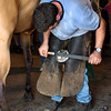 Farrier rasps at the horses hooves after trimming