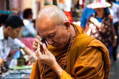 Buddhist Monk on the streets of Bangkok examines a religous relic. Bangkok, 2012