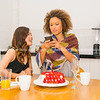 Breakfast time, at table two young women looking at mobile with red strawberry covered pavlova on table.