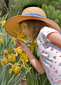 a child in a straw hat smelling flowers