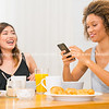 Breakfast time, at table two young women looking at mobile happily laughing together.
