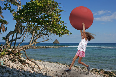 a little girl running on a tropical beach with a red ball