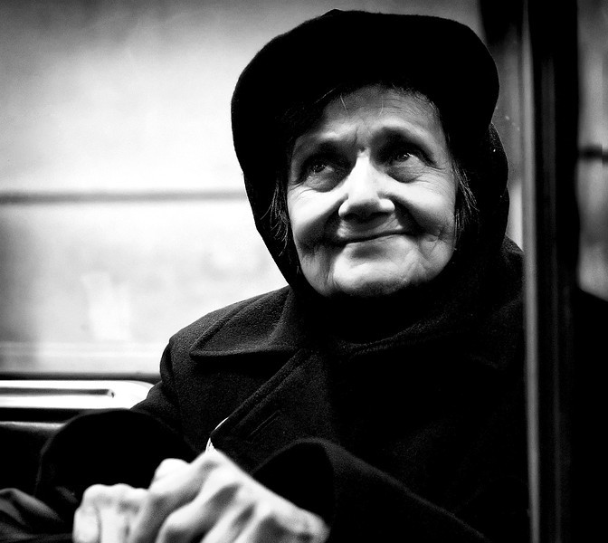 Black and white photo of an elderly lady travelling alone on the subway