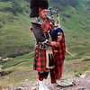 A Scottish piper plays his bagpipes alone among the cool hills of Scotland