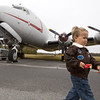Graham Cutis-Lashley, 3, hangs out on the taramak in his aviator jacket Saturday morning in front of the C-54 'Spirit of Freedom'.  Graham is the youngest member of the EAA, chapter 960 (Experimental Aircraft Association).   The aircraft was part of the Berlin Airlift program that brought food and supplies to Berlin residents cut off by Soviet occupants in 1948.  The plane, still in service, has been transformed into a museum and travels to airshows.  It is known as the 'Berlin Candy Bomber' made popular by it's pilot Co. Gail S. Halvorsen, USAF (ret.) who was called 'Uncle Wiggle Wings' by the Berlin children because he would wiggle the plane's wings to let the children know he was going to do a candy drop where bars of chocolate and such tied to little parachutes were tossed out of the plane as it flew over.  The historic plane is on display at Dillon's Aviation at the Pitt County Airport.