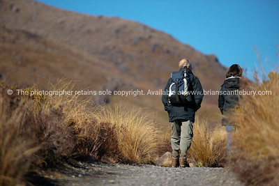 Trampers head off on the Tongariro Crossing, in New Zealand's Tongariro national Park. New Zealand photographic stock images. Model Release; no.