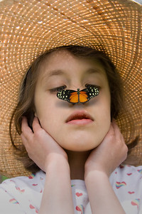 a child in a straw hat with a butterfly on her nose,