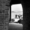 Two men watch the ocean through an archway at Boston Harbor