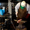 A New England blacksmith concentrates as he hammers his red hot wrought iron work
