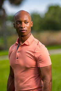 Portrait of a handsome African American bald man wearing a pink polo shirt