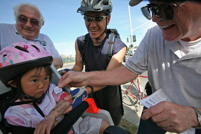 "Father Shane Shih displays his daughter's fore arm which reads, ""Bike to Work"" while she is getting a sticker.  They stop by for coffee and bagels at Gateway Blvd., and E. Grand Ave., in South San Francisco while en route to work at Genentech. This was the first day Shane took his daughter biking with him.  It was one of 22 locations throughout San Mateo County sponsored by the Peninsula Traffic Congestion Relief Alliance and the Silicon Valley Bike Coalition. Today was Bike to Work Day held throughout San Mateo County and San Francisco.  It is part of a national event to promote health, exercise and environmental well being.  By 9:30am, there were 258 bicyclists counted at the location.  Bicyclists were offered water, coffee, fruit and bagels as they stopped at the station on their way to work."