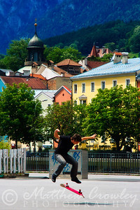Skateboarder performing a kick-flip in a square in Innsbruck, Austria