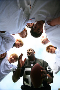 "Raider linbacker Morrison huddles up with kids at Town School for Boys in San Francisco & instructs a play during a football scrimage. As part of ""NFL Take a Player to School Day"", Oakland Raider LB, Kirk Morrison visited Town School for boys as a guest of third grader Mason Farley.  The visit included a stop at the principle's office to sign autographs; a school rally in the gymnasium and sports fitness activities. Its all part of the NFL's Play 60 campaign to encourage youth to exercise 60 minutes a day.  Morrison was among 34 NFL players participating in the event."