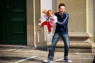 Father catching his daughter and twirling her on the streets of Lucerne, Switzerland