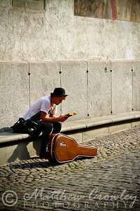 Young musician reading a book in the streets of Lucerne, Switzerland