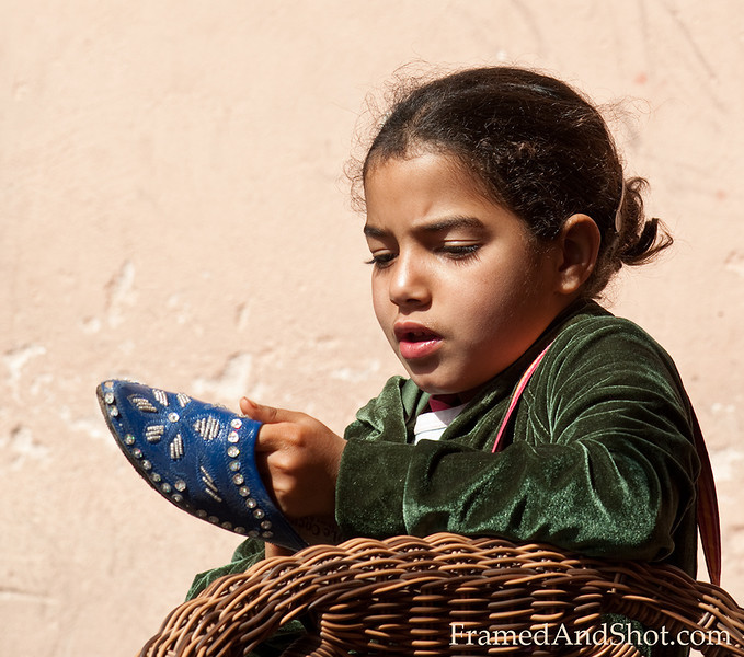 <b><center><em>The Shoe girl of Marrakesh  <br> Marrakesh is known for its soft leather moccasins, they are colorful and with nice decorations.