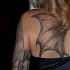 """De tattoes die mij zo troffen zijn de drakenvleugels op haar rug. Ze maken deel uit van een grote draak die haar hele rug beslaat. Deze draak is gezet door de shop van een vriend , Tony   <a href=""""http://www.pigmentaltattoo.com/"""">http://www.pigmentaltattoo.com/</a>). Omdat Lana's huid tatoeages moeilijk accepteert moeten ze met een ronde naald worden ingekleurd in plaats van met een platte. Dat kost veel extra tijd. Deze tatoeerder neemt  alle tijd voor haar ; zo kostte het tatoeëren van de draak acht tot negen sessies van elk anderhalf tot vier en een half uur. Lana heeft helaas ook andere ervaringen. Voordat ze Tony leerde kennen heeft ze bij veel verschillende tattoo shops afbeeldingen laten plaatsen. De eerste bleek alleen uit te zijn op snel geld verdienen en heeft het werk afgeraffeld. De tweede shop beviel haar goed maar die verhuisde helaas. Over een deel van haar linkerarm is ze niet tevreden, één van de tattoes daar  is in één keer opgezet, wat met haar huidtype nooit had mogen gebeuren. Ze is te diep geprikt, wat tot bloedverlies en littekenweefsel heeft geleid.<br /> <br /> Terug naar de draak. Toen Lana 15 jaar was begon ze aan de draak op haar rug. Op de onderrug kwam een draak in de breedte. Deze is ontworpen door een vriend die haar op het hart drukte om te wachten tot ze uitgegroeid zou zijn alvorens hem in de lengte verder uit te werken. Het lange wachten begon en na zeven jaar was het zo ver en kon de draak in zijn volle glorie oprijzen tot het symbool dat nu haar rug siert. <br /> Lana vertelt me hoe hij is geworden hoe hij nu is. Ze begon met zelf schetsjes te maken. Daarna vroeg ze aan een vriendin, die beter kan tekenen, om ze om te zetten in een ontwerp. Aldus geschiedde. Met het ontwerp toog ze naar de tatoeëerder. Tony zag meteen dat bepaalde aspecten niet konden; hij kan erg goed tekenen en bracht wijzigingen aan. Per sessie is het ontwerp vervolgens aangepast, in overleg met haar. Uiteindelijk is de draak veel geavanceerder geworden dan h"""