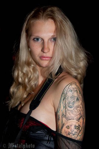 """Ik leg haar uit wat ik van haar wil en ze blikt indringend in de lens van mijn camera. Wij gaan zitten en dan verzink ik voor een uur in de wereld van Lana.<br /> """"Ik wilde tattoes hebben vanaf het eerste moment dat ik wist dat ze bestonden; ik was toen 10 jaar. Ik kan niet uitleggen waarom maar ik heb steeds het gevoel gehad dat het iets is dat bij mij hoort"""", zegt ze. """"Mijn eerste tattoe liet ik zetten toen ik 13 jaar was, het was een klein draakje. Mijn ouders vonden het geen goed idee maar ik was zó overtuigd dat ze het uiteindelijk toestonden. Na die eerste tattoe was het hek van de dam en volgden er steeds meer. De tweede op mijn veertiende, op de rechterbovenarm en op mijn vijftiende kwam er een draakje op mijn linkerbovenarm. Ik ben nu 26 en nog steeds blij met mijn tattoes. Maar ik besef nu wel dat het fout was om er zo vroeg mee te beginnen, want je moet eerst uitgroeien. Al mijn tattoes moesten worden bijgewerkt toen ik uitgegroeid was. Als ik kinderen zou hebben zou ik ze verbieden om zich zo jong te laten tatoëeren. Al mijn tattoes zijn uniek, ze horen bij mij en hebben symbolische betekenis. Allemaal, op één na, dat is een tribal op mijn onderrug. Die heb ik laten zetten uit verveling; het is een plaatje uit een boek.""""<br /> Lana blijkt een boeiende vrouw te zijn, die niet uitgepraat raakt over het verhaal van haar tatoeages. Ze zijn ook zó belangrijk voor haar, zó'n deel van haar wezen, iets waar ze trots op is en waar ze veel , heel veel ,voor over heeft. Bij alle personen die ik interview is er sprake van een tol die betaald wordt voor het dragen van tattoes, maar bij haar is die tol wel erg hoog. Luister maar.<br /> <br /> <br /> <br /> (DSC_7810_1wm)"""