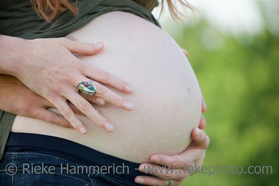 Woman's pregnant belly with hands from both Parents – Germany, Europe