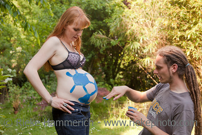 Munich, Bayern, Germany – May 24, 2010: Young Man with dreadlocks finger painting on a woman's pregnant belly in English Garden in Munich, Germany. The woman is eight months pregnant.