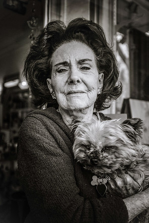 "Ellen, a Philly native, and her dog, Angel. She rescued the dog from a life of 'breeding offsprings for sale while living in a small cage' and they've been fast friends ever since.   We had a nice chat on the sidewalk, interspersed with ""give mommy a kiss"" injunctions every so often; Angel complied willingly enough. I noticed a little angel pin with a shamrock on her sweater: she wears it always, in memory of all previous ""Angels"" and her dad who was Irish."