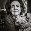 """Ellen, a Philly native, and her dog, Angel. She rescued the dog from a life of 'breeding offsprings for sale while living in a small cage' and they've been fast friends ever since. <br /> <br /> We had a nice chat on the sidewalk, interspersed with """"give mommy a kiss"""" injunctions every so often; Angel complied willingly enough. I noticed a little angel pin with a shamrock on her sweater: she wears it always, in memory of all previous """"Angels"""" and her dad who was Irish."""