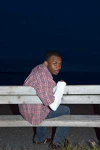 An African-American male sitting on a bench.