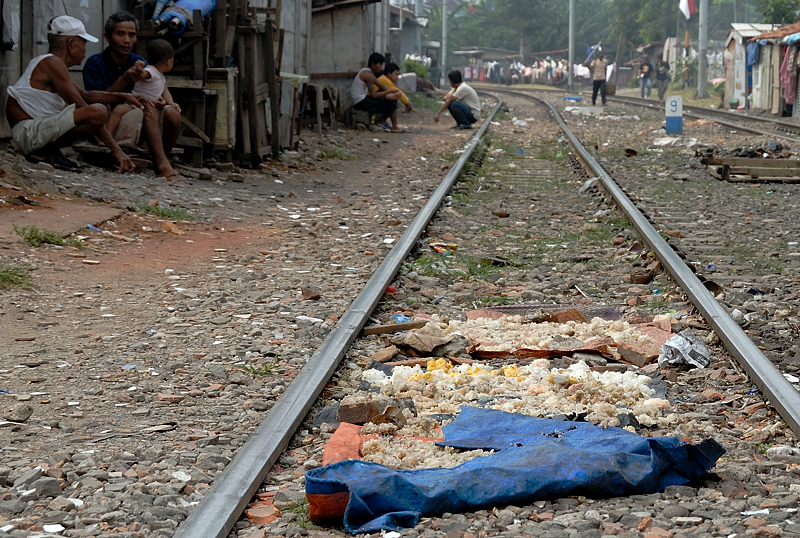 Food is left to dry on mats on the railway.  It is the only open space available to some dwellers.
