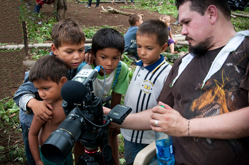 The return of the families is being filmed by a documentary crew. This is a new experience for these children, who are for the first time seeing their community on video.