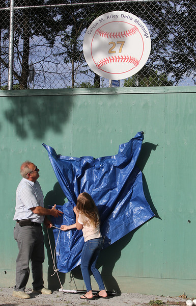 Whiffle ball field at Mulligan Park, off Plain Street in Lowell, is dedicated to former Lowell resident Calvin Riley, who was killed while playing Pokemon Go last summer in San Francisco. Parks commissioner Tom Bellegarde and Cal's sister, Bria Riley, who turns 11 tomorrow, of San Mateo, CA, unveil a sign with one of Cal's numbers. (SUN/Julia Malakie)