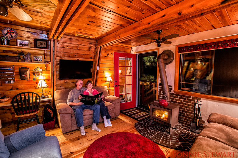 """Roger and Cheryl looking at their """"BOOK"""" for the first time.  Book design and photos of their time in San Diego were taken by Bonnie.   The reveal took place in their enchanted cabin in the White Mountains, Arizona"""