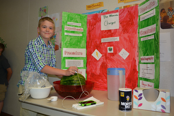 Dayne Niehart displays his sixth grade science project, which is a watermelon that charges an iphone. The iphone was charged by electrons created in the melon by putting ice and salt in the bowl.