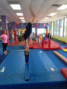 Sam dismounts from the balance beam during the show for parents at the Little Gym
