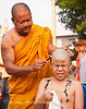 A Young Shan Boy Grimaces As His Head Is Shaved By Monk